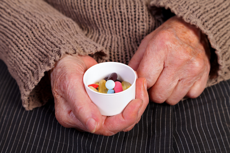 Close up of an elderly hand holding a box with supplements